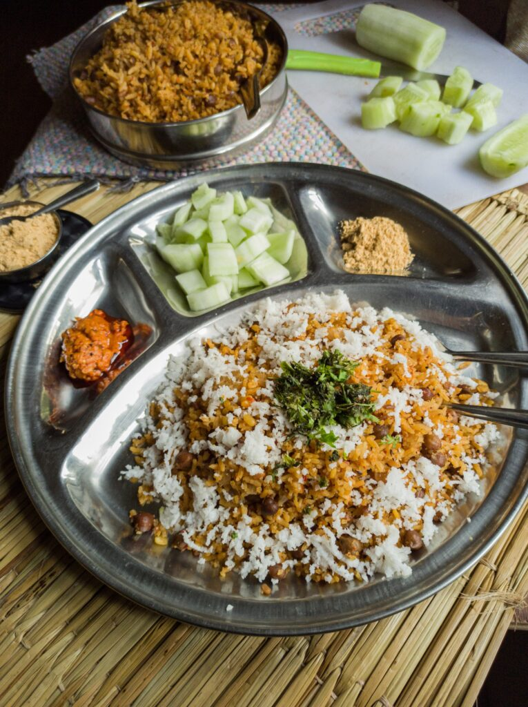 Usili Upma Rice served in a steel plate with cucumber pieces, chutney powder, pickle and garnished with fresh coconut and finely chopped coriander leaves.